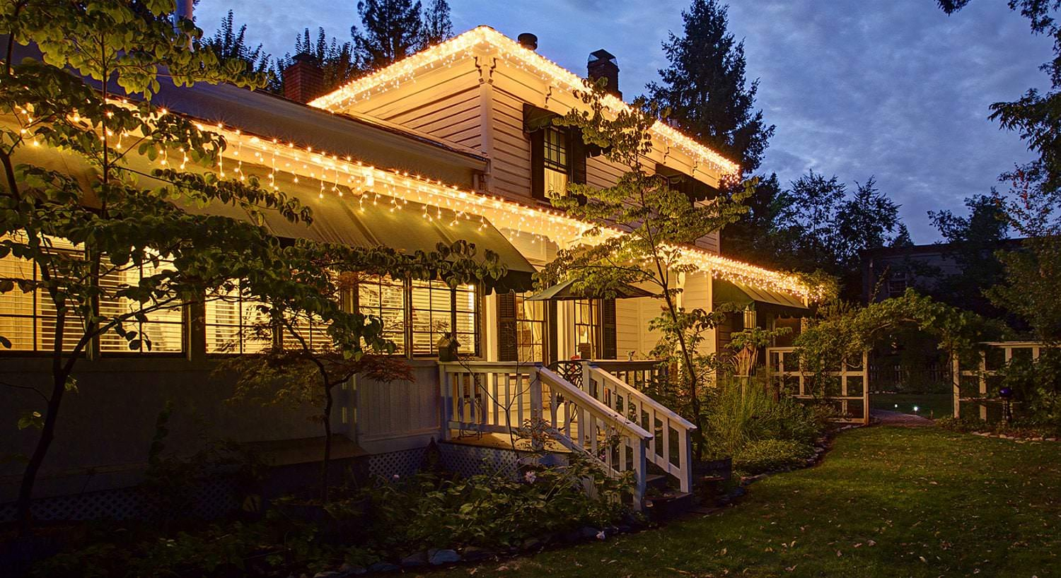 Exterior view of Dunbar House and green lawn at dusk brightly lit with interior lights and exterior twinkle lights