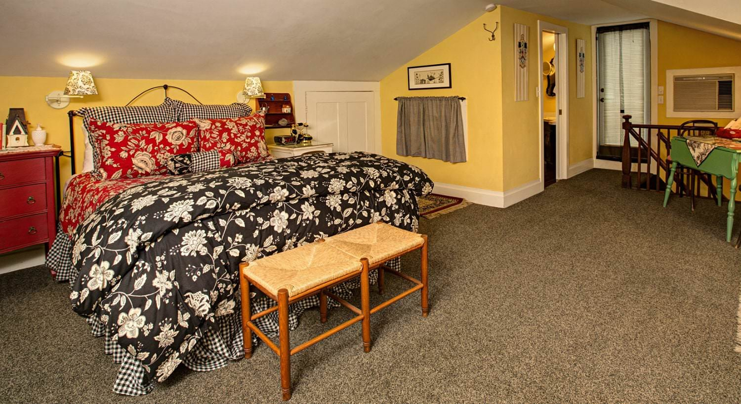 Spacious yellow room, vaulted ceilings, tan carpet, black, red and white covered bed, red nightstand, and wood table and chairs