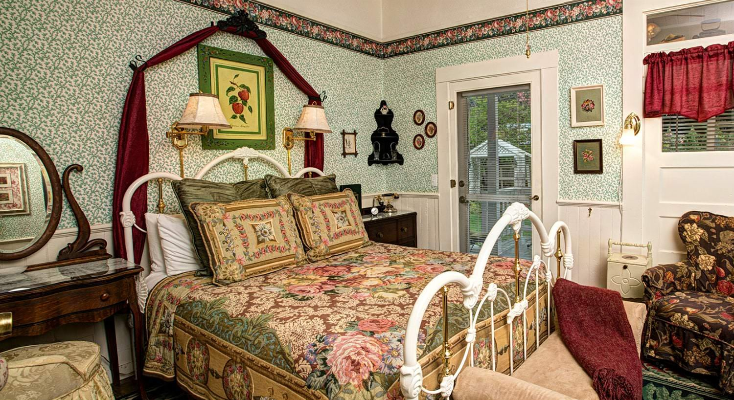 Green and white papered guest room, wood floors, floral covered bed with wood nightstands, floral upholstered chair, and French door