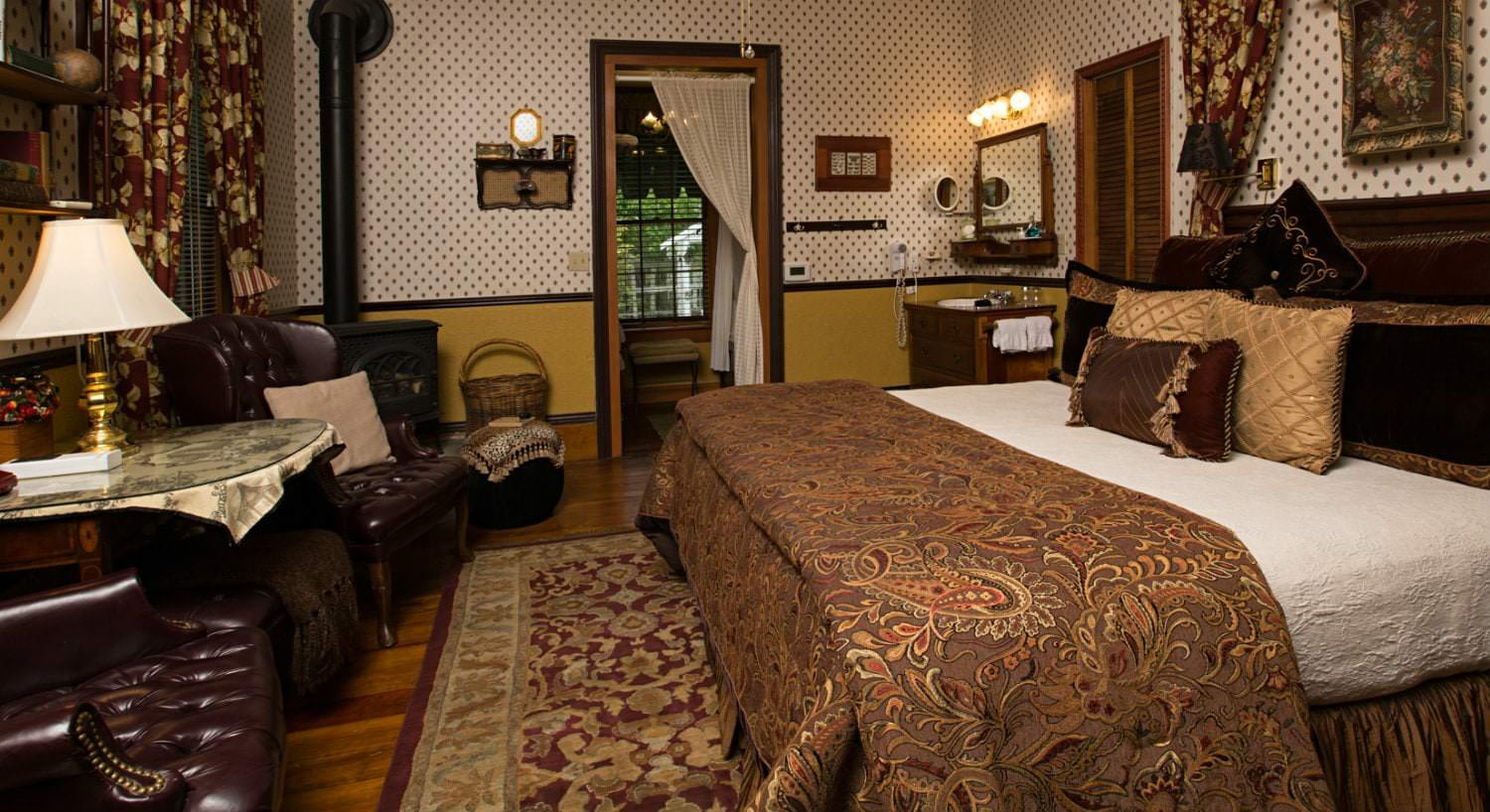 Guest room with brown paisley and gold covered bed, wood floors, area rug, dark leather chairs flanking glass top table