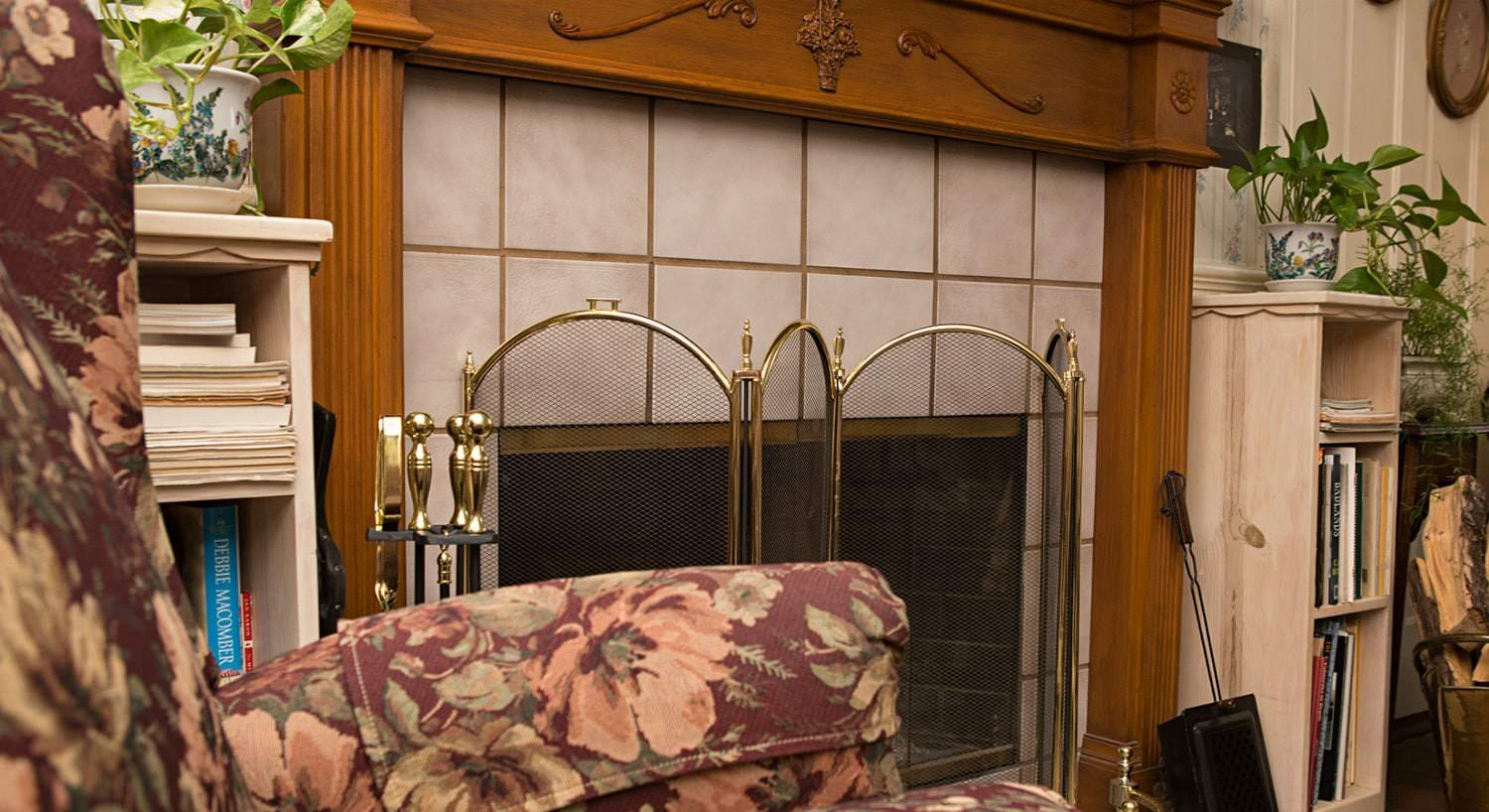 Close-up view of the sitting room fireplace with white tile, stained wood mantel surround, and gold screen