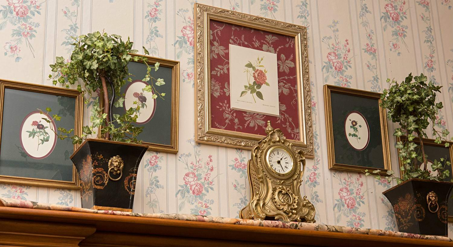 Sitting room fireplace mantel topped with gold clock, two plants in black pots, floral wallpaper with gold framed floral pictures