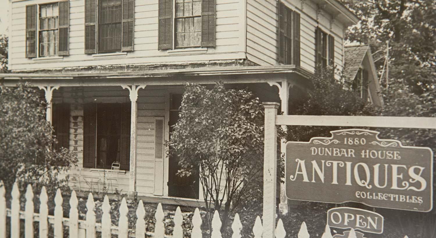 Old black and white photo of the Dunbar House and it's sign for antiques and collectibles