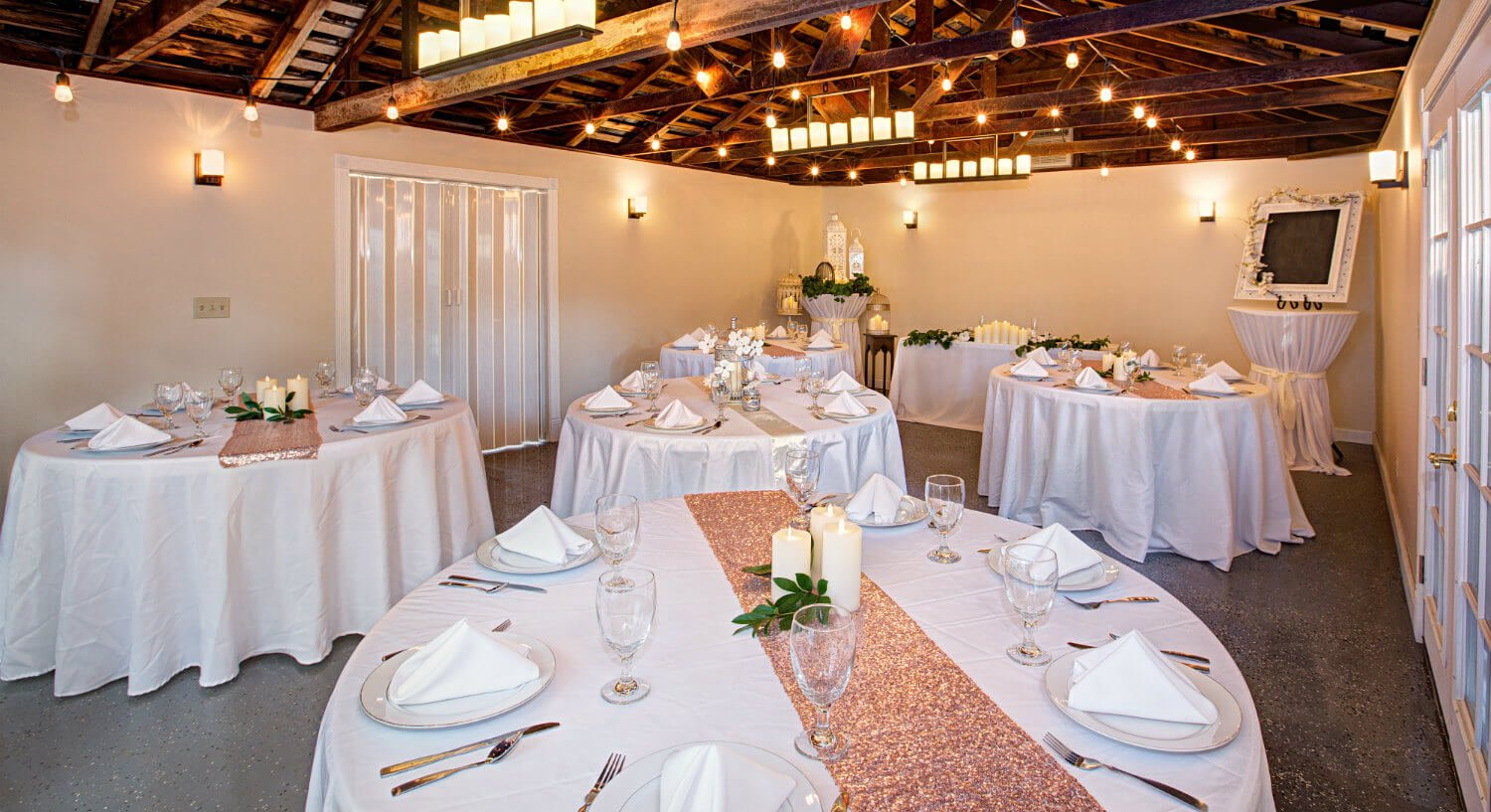 white round tables set for event with white linens, red runners, candles, in room with barn style peak ceiling, beige walls