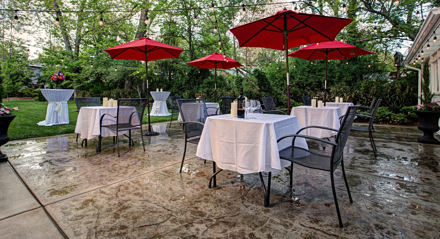 rows of square tables on patio with white linens, black iron chairs, red umbrellas separate each set of tables