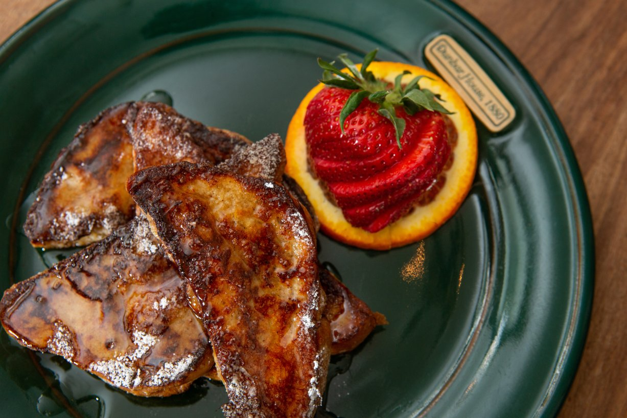French Toast: Four slices of french toast covered with syrup adorn this green plate with a fanned strawberry garnishing the dish. The inn logo is visible on the plate.