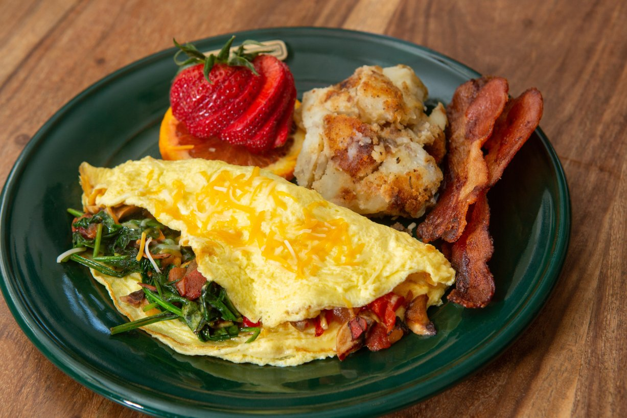 A hearty looking plate with an omelette, two strips of bacon, country skillet potato, and a strawberry garnish.