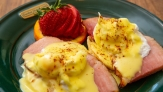 Eggs Benedict: Ham slices with poached egg, covered in a creamy yellow sauce and seasonings. A fanned strawberry on an orange slice garnishes this plate.