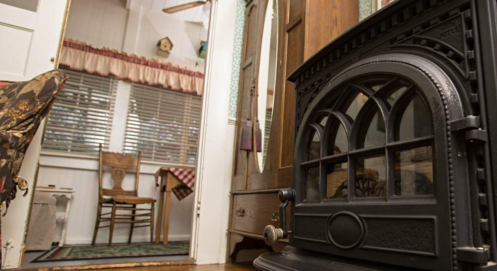 Close-up view of the Cedar room's black iron fire stove next to a wood cabinet