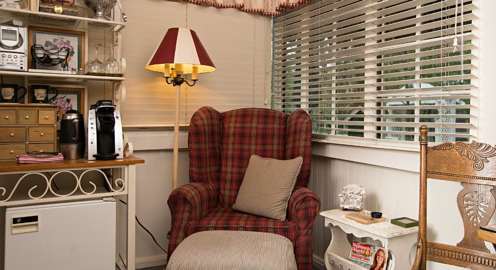 Red plaid upholstered chair with lamp, two windows with white blinds, and a beverage cart with Keurig, teapot, glasses, etc.