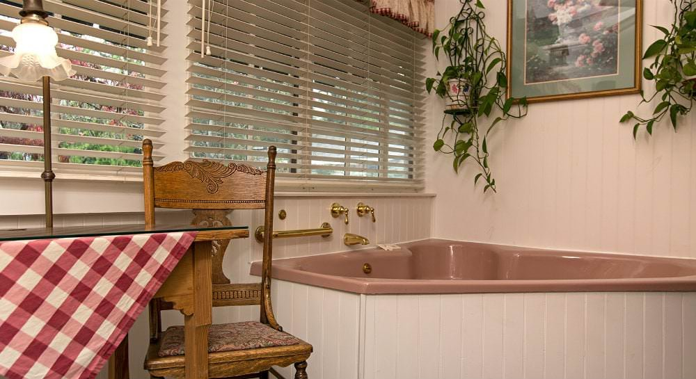 Bathroom with pink garden tub, white paneling, and two windows with white blinds