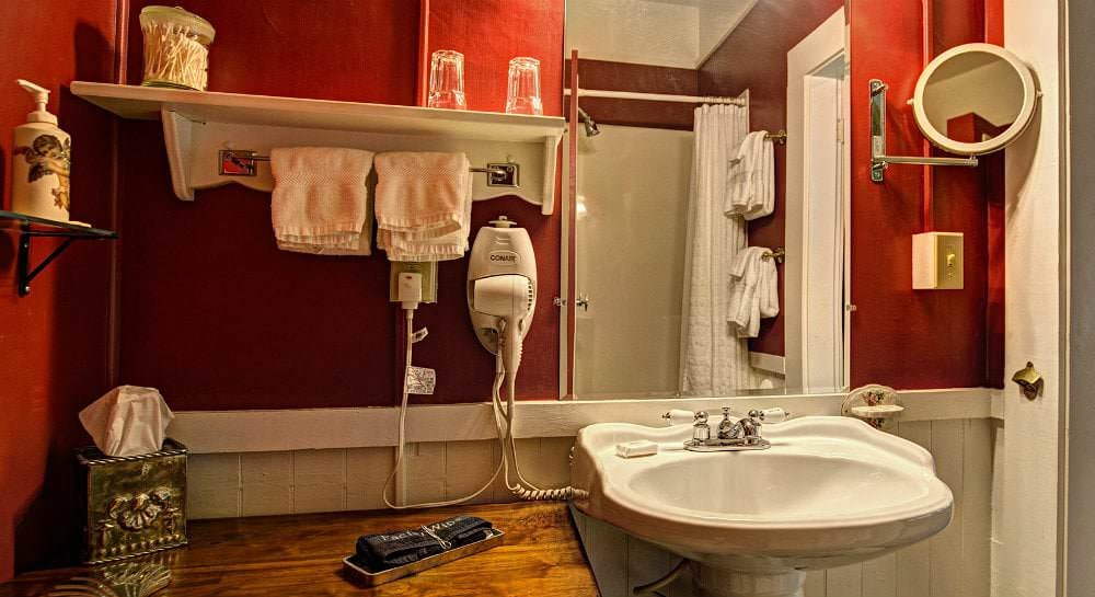 Red and white bathroom with white pedestal sink and white towels