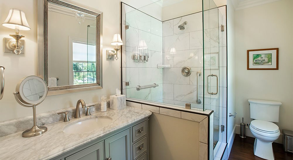 Glass shower next to bathroom vanity with makeup mirror as well as mirror on the wall.