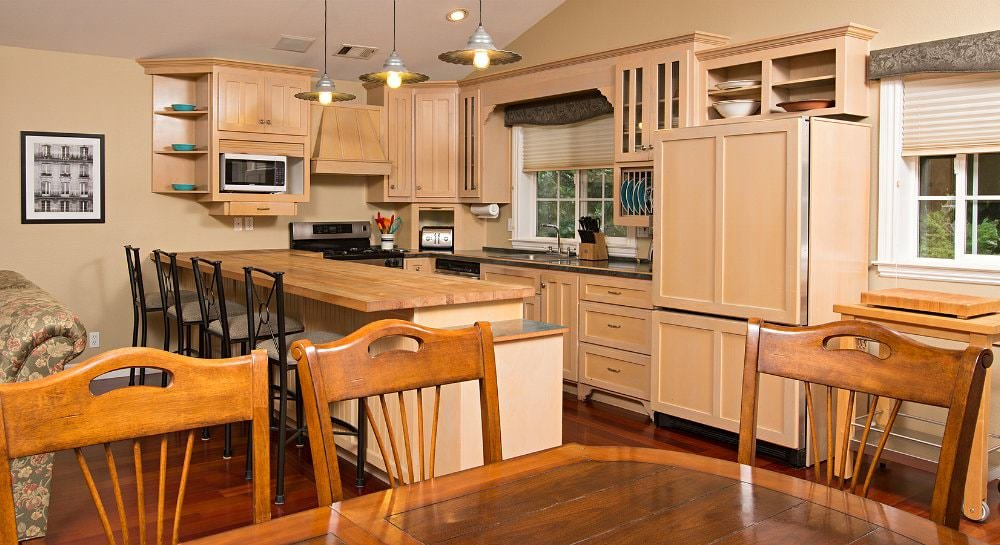 Beige kitchen with cherry wood floors, blonde cabinets, and butcher block bar top with four stools