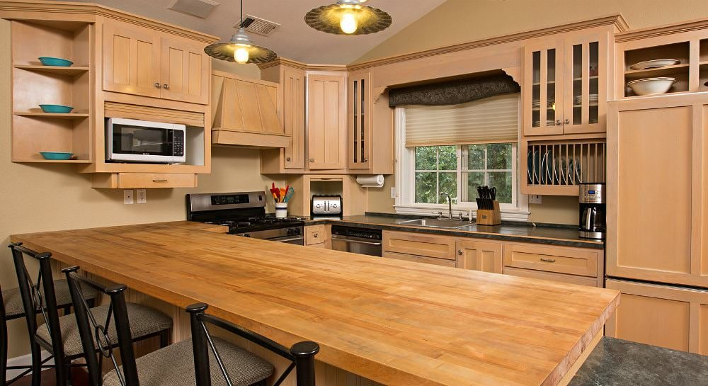 Beige vaulted kitchen with blonde cabinets, stainless appliances, sink window and butcher block bar top with four stools