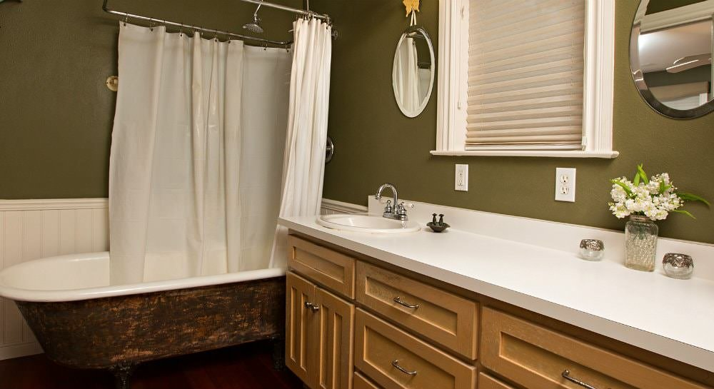Green bathroom with wood floors, large vanity, claw foot tub and window flanked by round mirrors