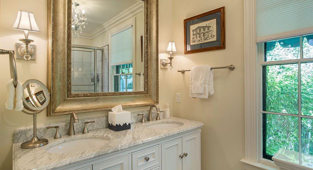 Bathroom vanity with twin sinks beneath mirror and window.