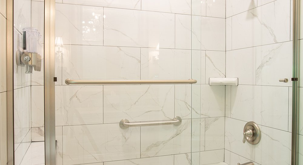 Glass shower with tile and stainless accessories.
