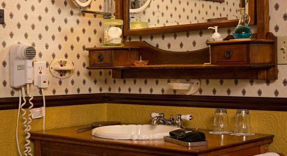 Wallpapered bathroom with wood vanity, white sink, stained wood mirror and shelf, and hairdryer