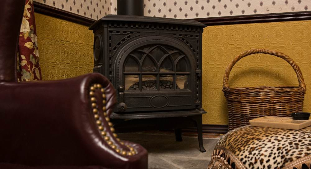 Close-up view of black iron wood stove on gray tile with glimpse of dark red leather chair