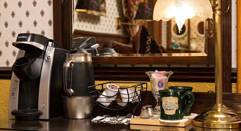 Close-up view of beverage station with Keurig, teapot, k-cups, green mugs and antique style gold lamp