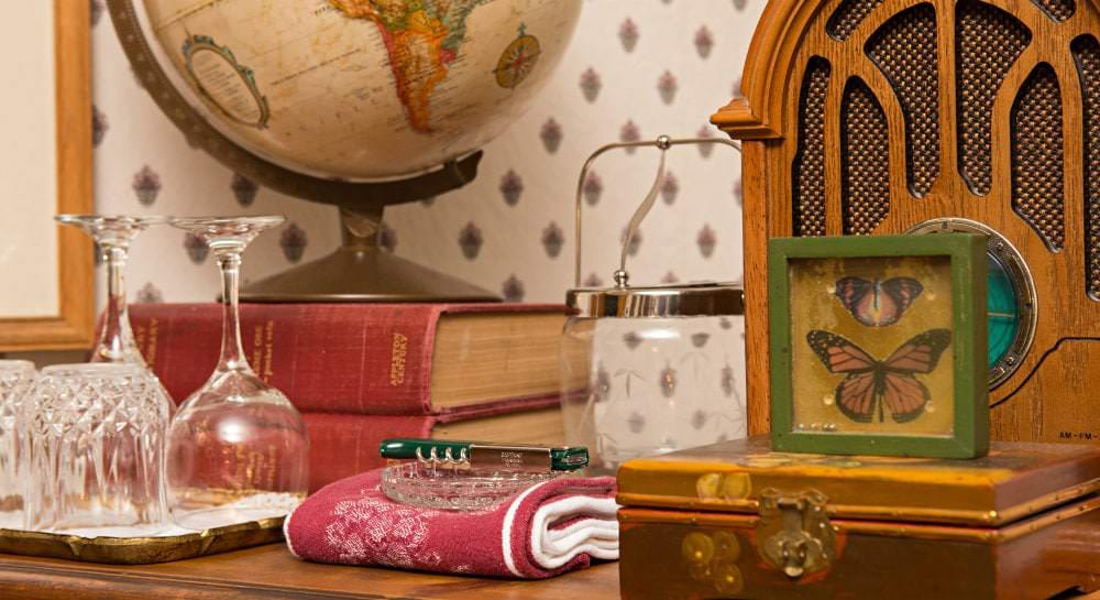 Close-up view of cabinet top with glasses, wine glasses, two red books and a globe