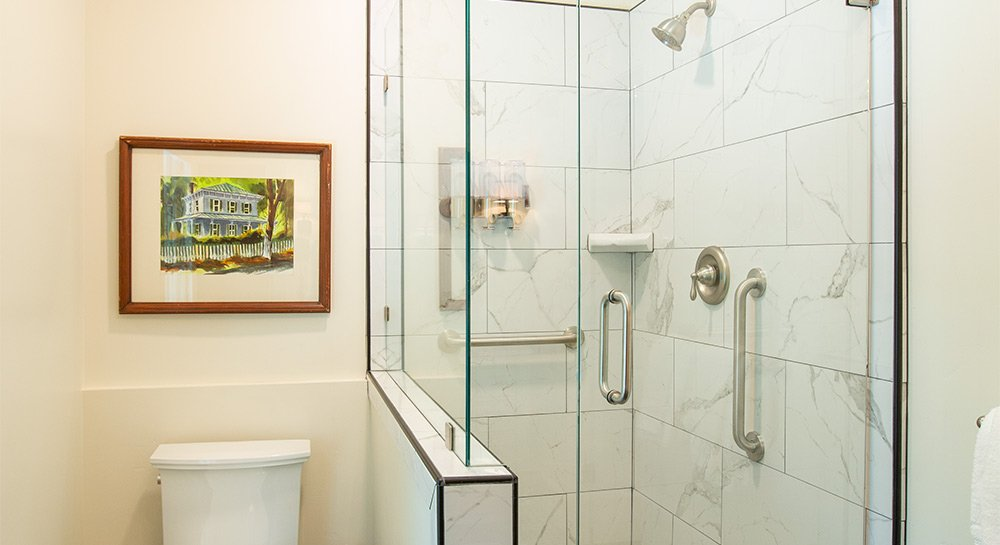 Enclosed glass shower next to artwork on the wall.