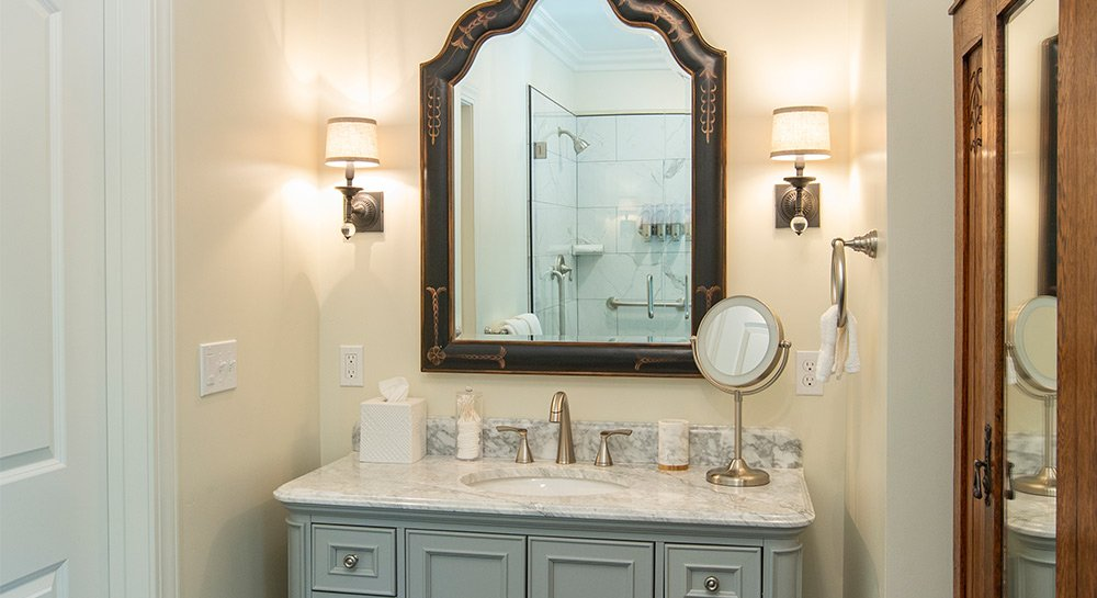 Bathroom vanity with large mirror hung above the sink. Twin lights flank the mirror.