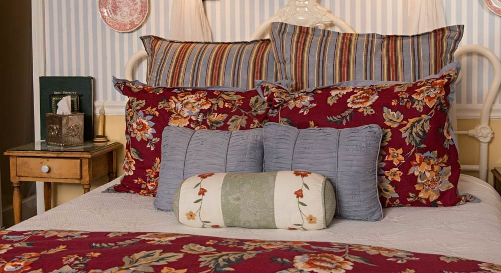 Close-up view of bed with red and blue floral bedding and striped pillows and a small wood nightstand