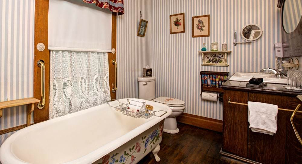 Bathroom with wood floors, white claw foot tub and stool, window with white shade and wood vanity and mirror