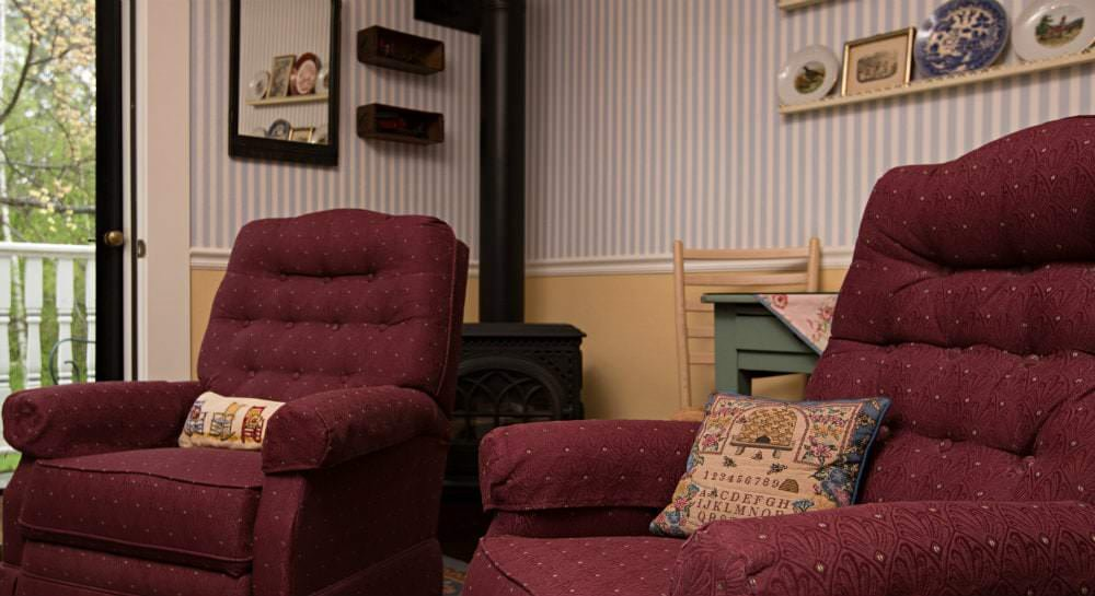 Two red upholstered chairs in front of a black iron wood stove
