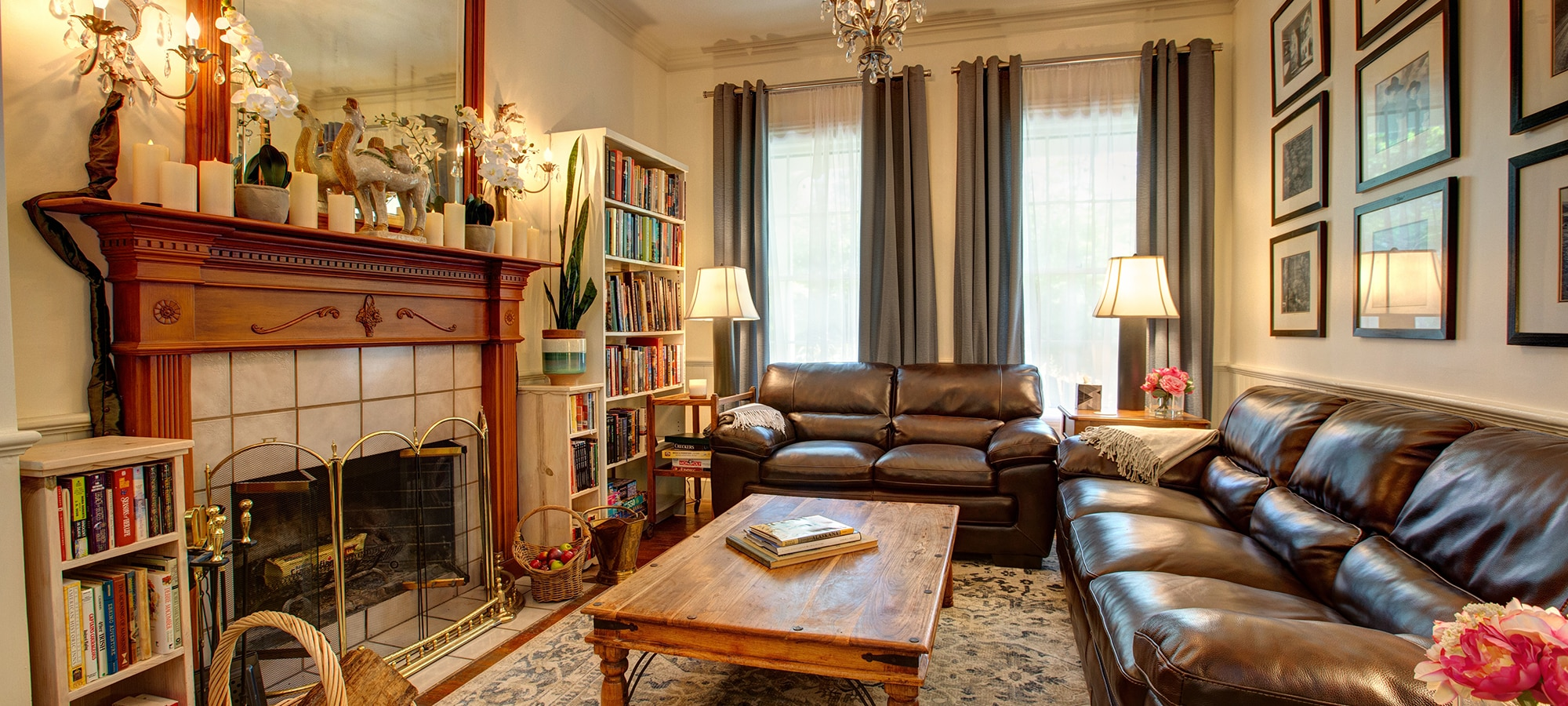 Side view of a social nook with love seat, couch, and fireplace. Many books fill cases flanking the fireplace and mantle.