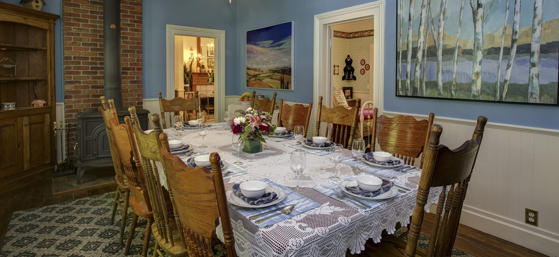 A sea blue dining room with antique wooden chairs around placesettings with a floral centerpiece and colorful artwork on the walls.