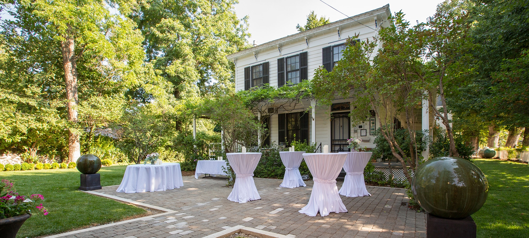 "An outdoor brick patio featuring white round banquet tables, and taller ""standing"" tables with decorative centerpieces. The house's porch area can be seen in the background."
