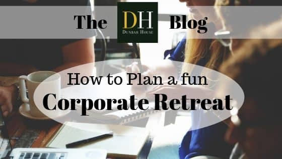 A Dunbar House Promotional Image reading: How to plan a fun Corporate Retreat, displayed in a white bubble superimposed over an image of people at a work table, and office supplies.