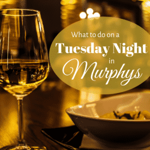 "Promotional Image: A white wine in wineglass, next to a bowl of pasta with the words ""What to do on a Tuesday Night in Murphys"" superimposed upon it."