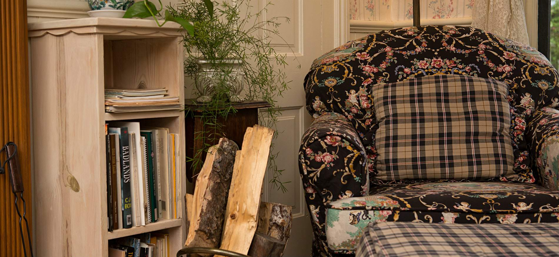 Black and pink floral and plaid chair with ottoman next to a wood shelf filled with books