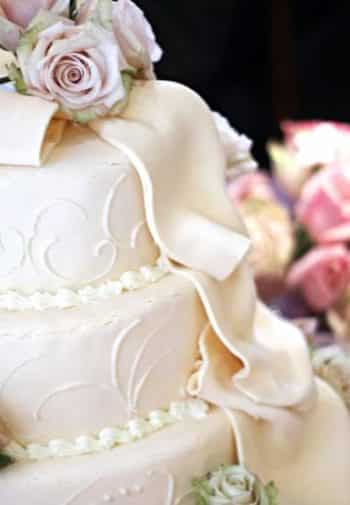 Close-up view of a white tiered wedding cake with decorative roses and cascading ribbon frosting