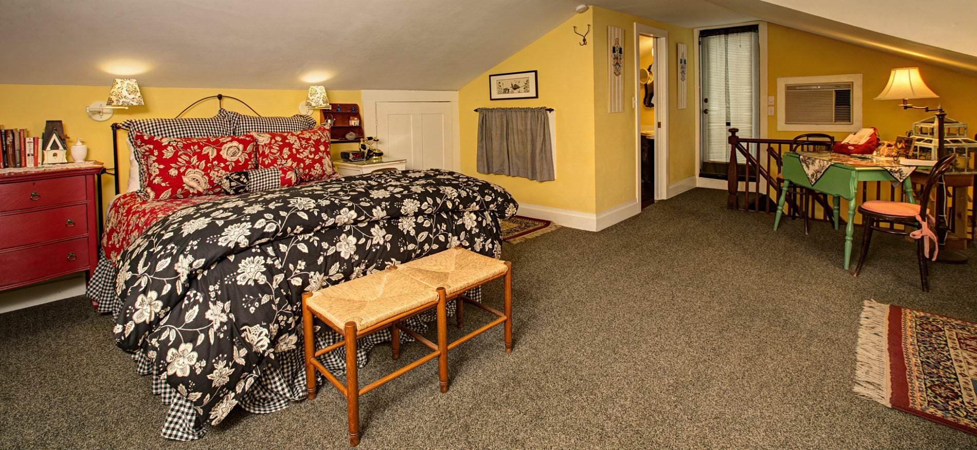 1. Spacious yellow room, vaulted ceilings, tan carpet, black, red and white covered bed, red nightstand, and wood table and chairs