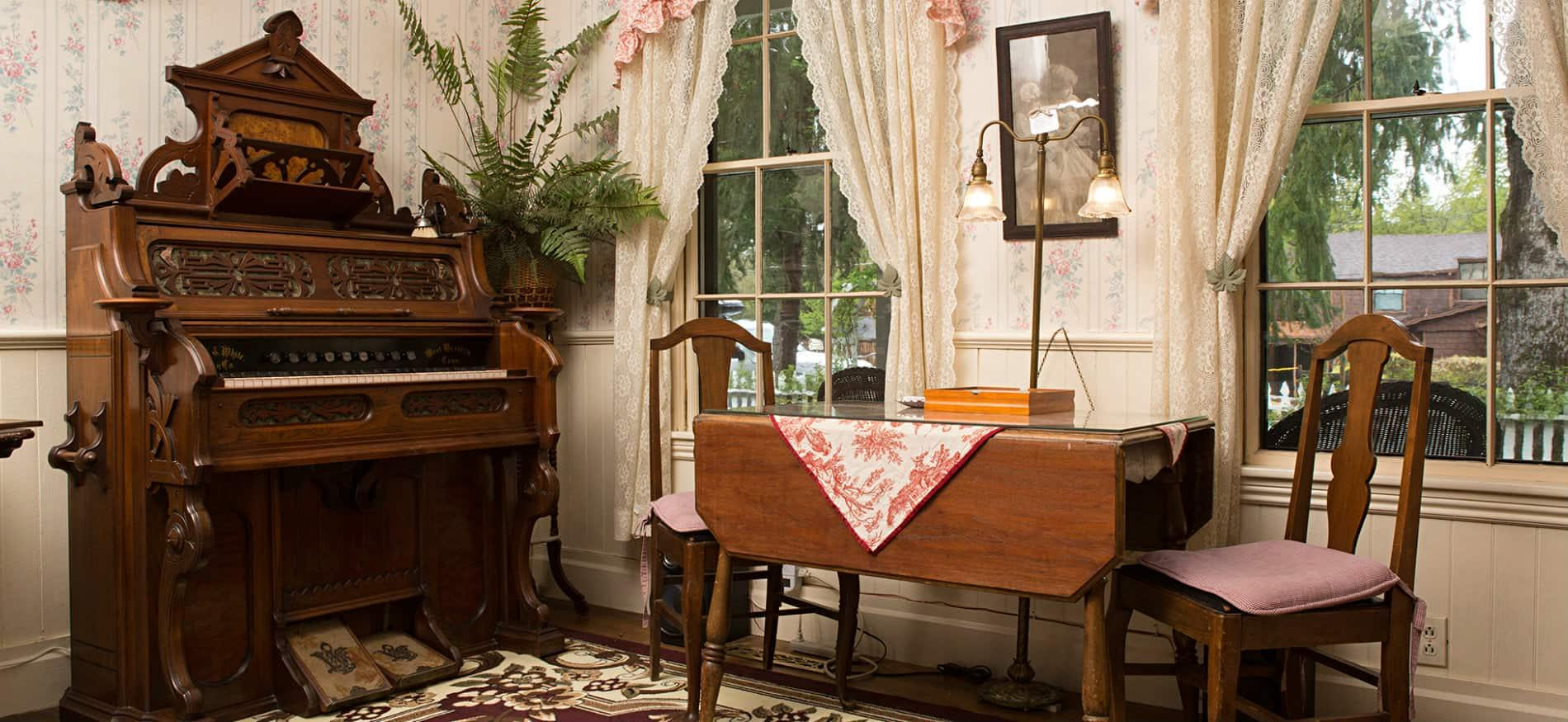 Ornate antique organ, wood drop-leaf table with two chairs, light floral wallpaper and two windows with lace curtains