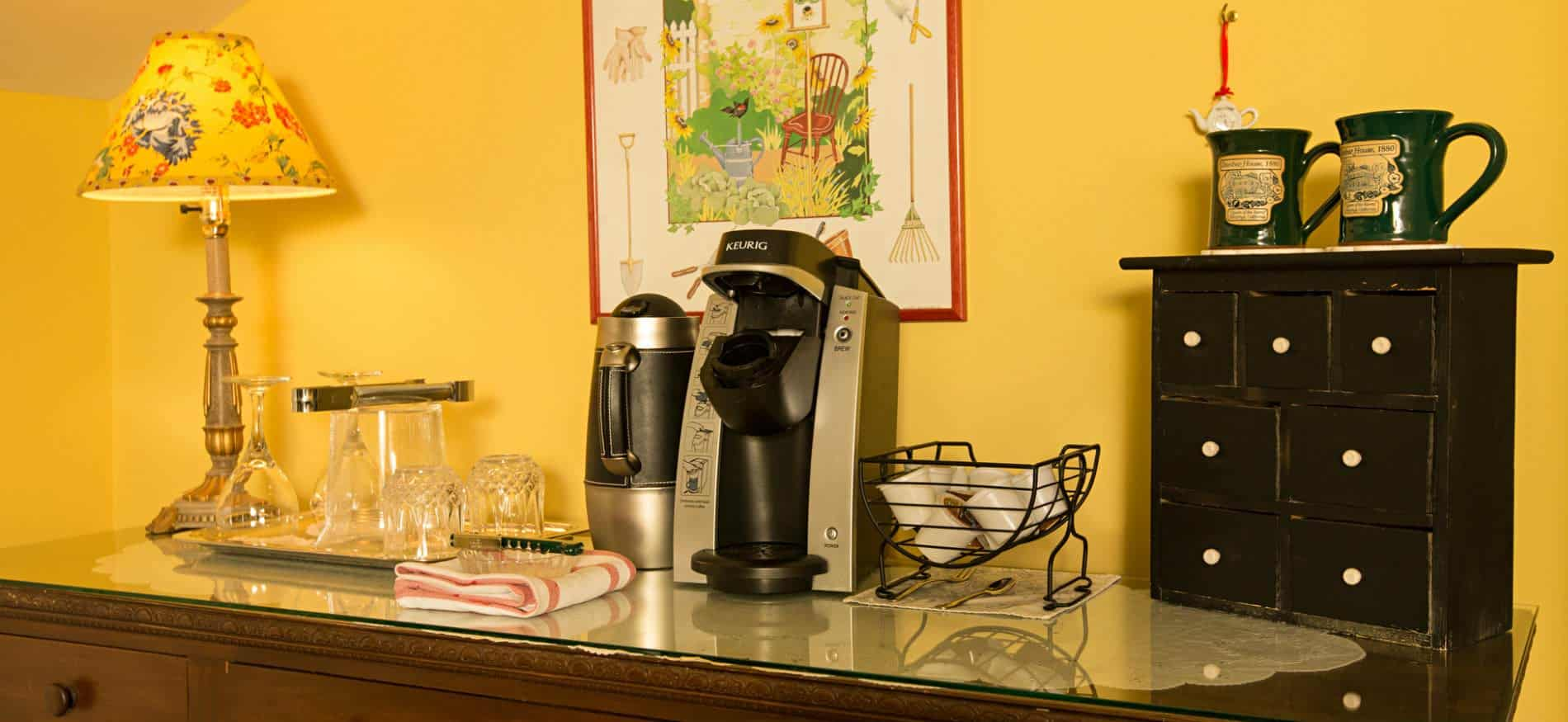 Close-up view of beverage station with floral lamp, Keurig, teapot, k-cups, coffee mugs, glasses and wine glasses