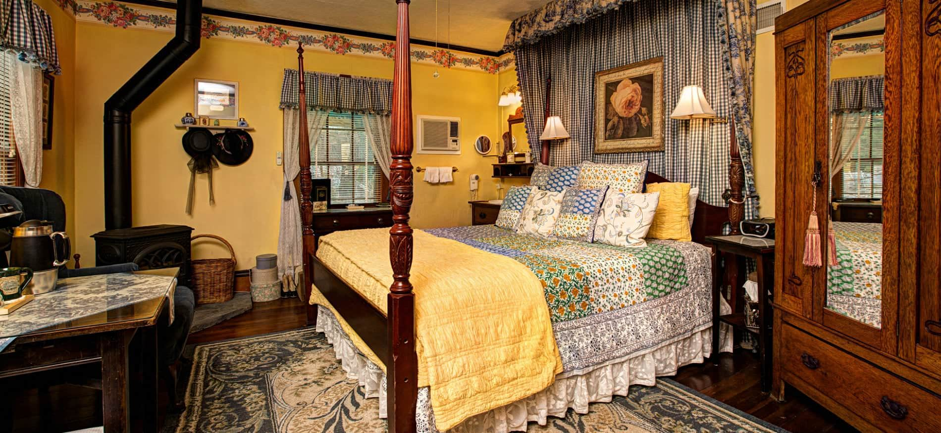 Yellow guest room with wood floors, area rug, colorfully covered four poster bed, and blue and white gingham window valances