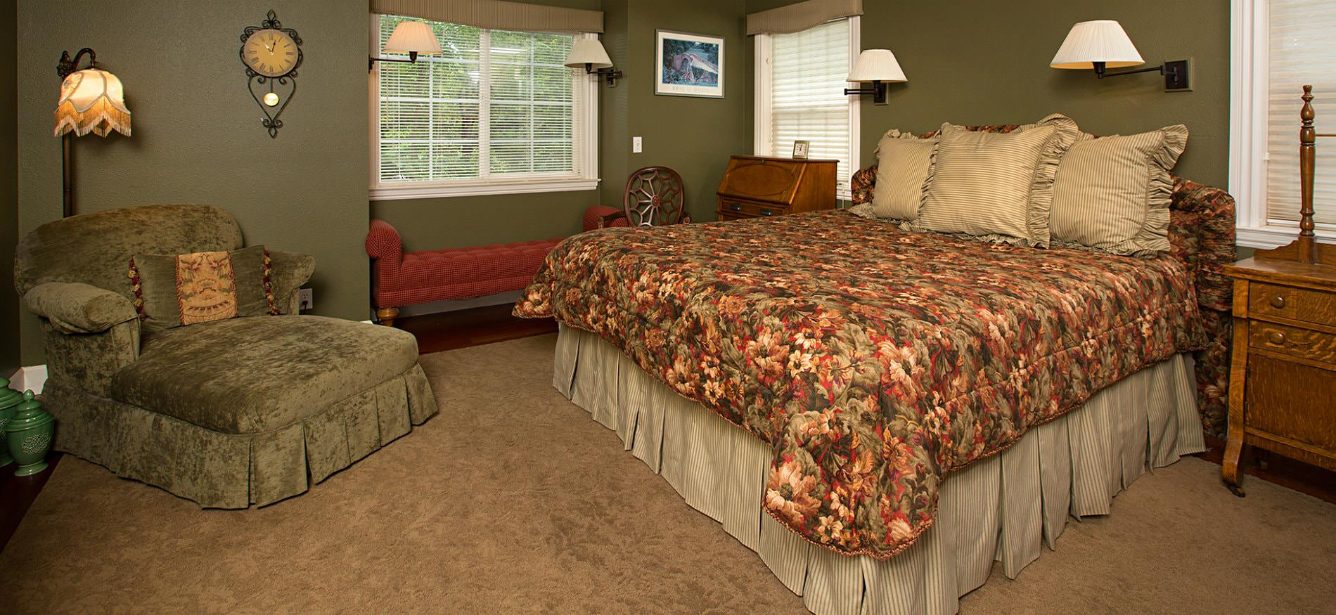 Sage green guest room with tan rug, floral covered bed, green upholstered chair, sconce lighting and three windows