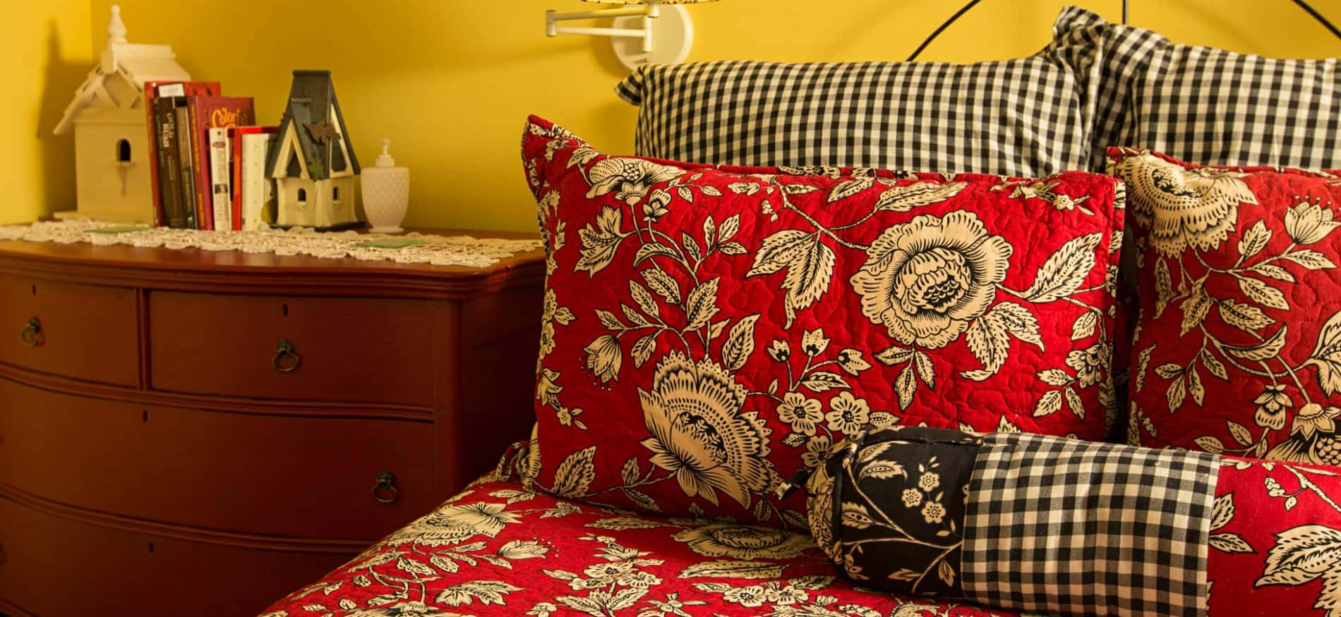 Close-up view of bed with red, black and white bedding and a nightstand chest topped with books and birdhouses