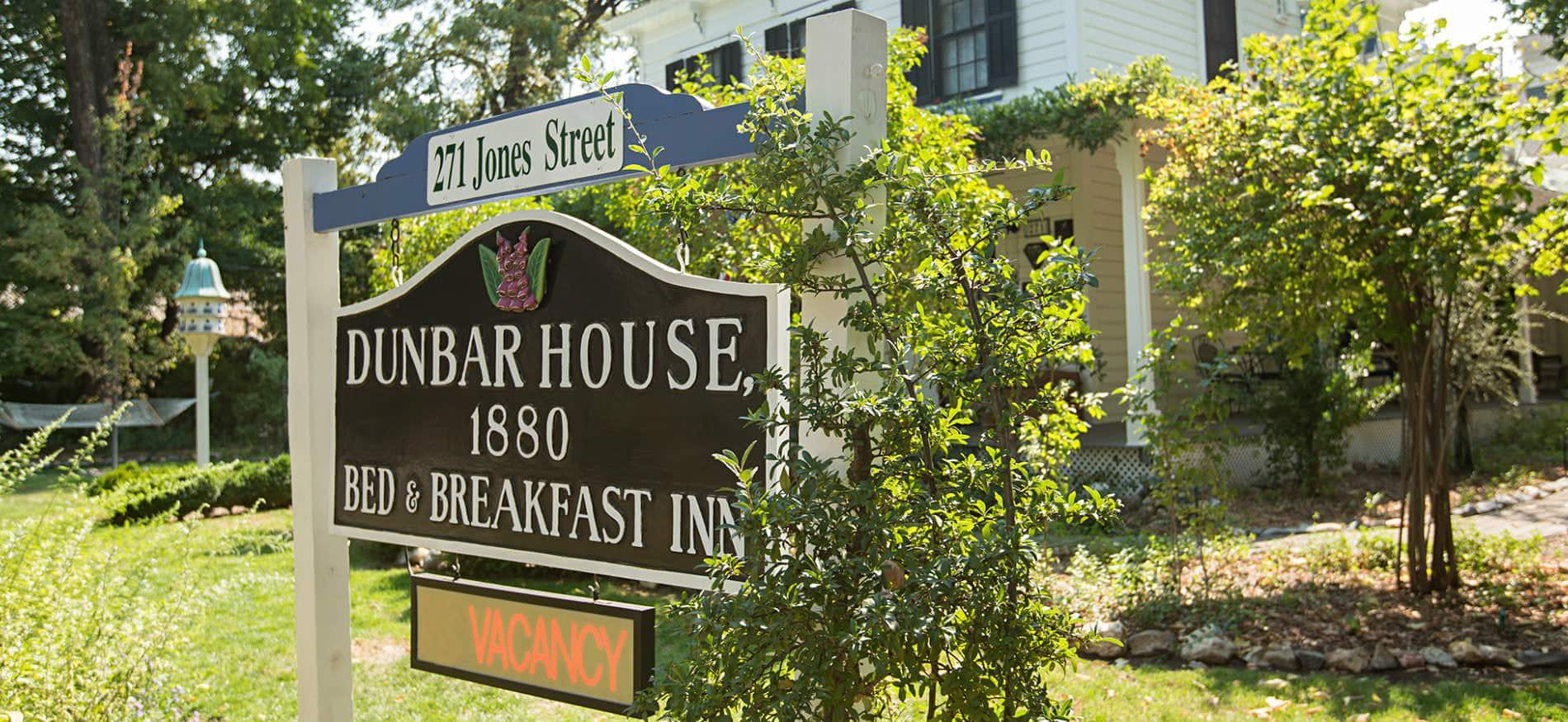 Close-up view of Dunbar House 1880 vacancy sign surrounded by greenery