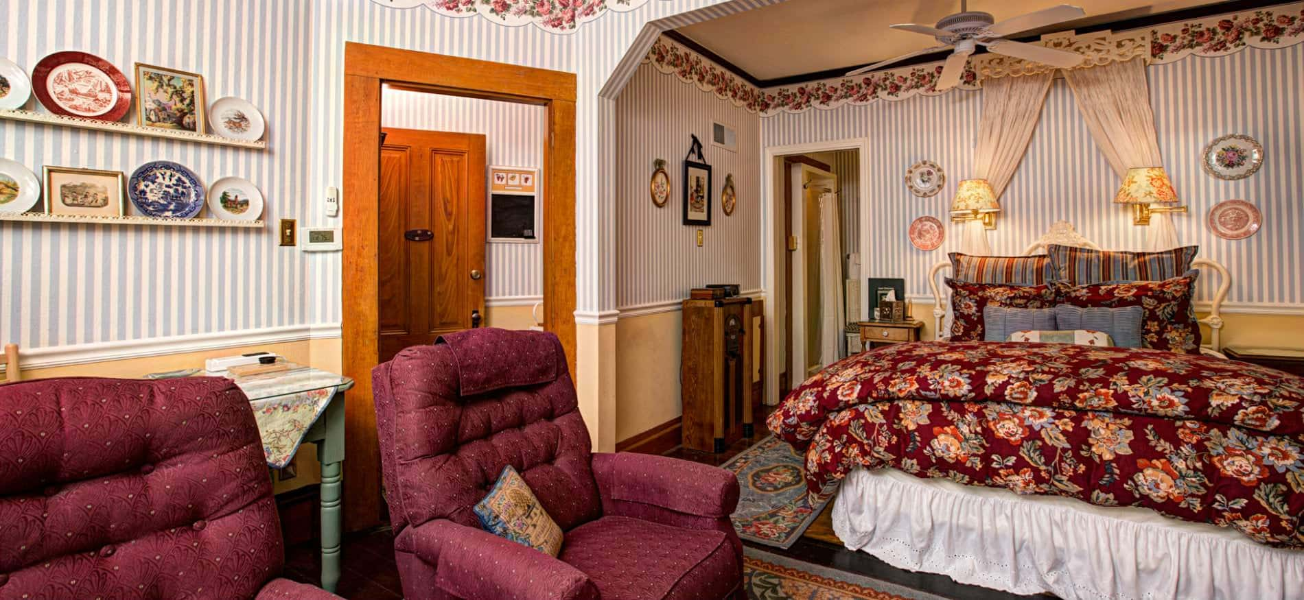 Spacious guest room with blue and white striped wallpaper, a red floral covered bed and two red upholstered chairs
