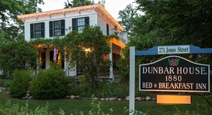 Exterior view of Dunbar House with white siding, black shutters, and twinkle lights surrounded by lush greenery