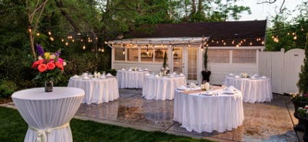 outdoor setting on patio in front of white cottage building, round tables set for event with white linens, red runners, candles, green lawn in foreground with bright flower arrangement on high table, trees in background