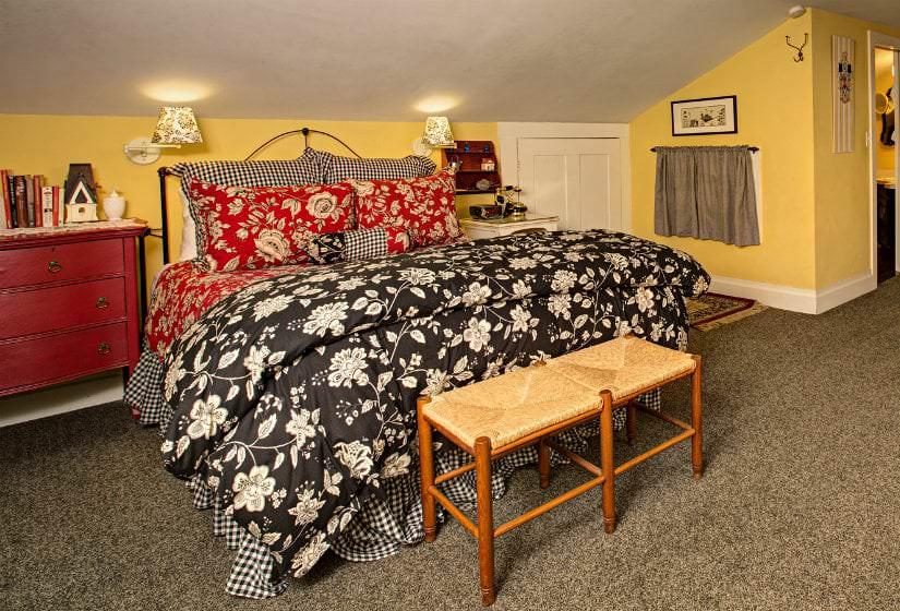 Spacious yellow guest room with vaulted ceilings, tan carpet, black, red and white covered bed and red nightstand