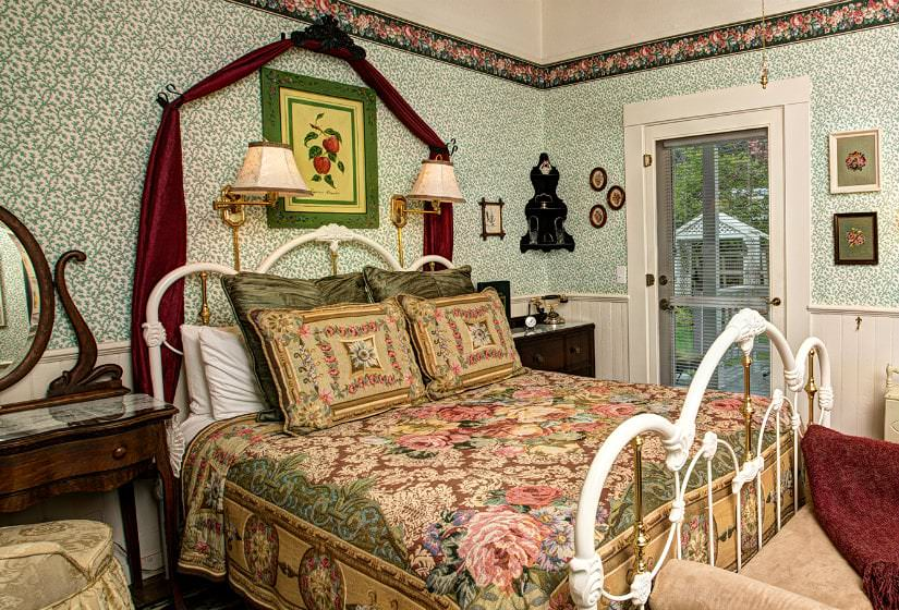 Green and white papered guest room, floral covered bed with wood nightstands, and French door